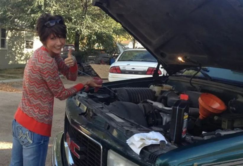 Women tyr to repair a used car.